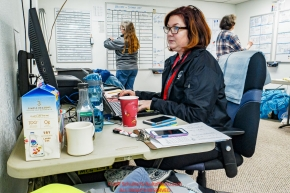 McGrath logistics volunteer Jodie Guest works the computer as swing-pilot Diana Moroney and Deb Miller coordinate loads in the background at the McGrath checkpoint during the 2018 Iditarod race on Wednesday March 07, 2018. Photo by Jeff Schultz/SchultzPhoto.com  (C) 2018  ALL RIGHTS RESERVED