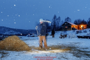 Longtime volunteer Brad VanMeter rakes straw in the early morning hours at the ghost-town checkpoint of Iditarod on Saturday, March 10th during the 2018 Iditarod Sled Dog Race -- AlaskaPhoto by Jeff Schultz/SchultzPhoto.com  (C) 2018  ALL RIGHTS RESERVED