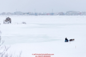 Mike Williams Jr. runs on the slough heading towards the Unalakleet checkpoint in the background on Monday  afternoon March 12th during the 2018 Iditarod Sled Dog Race -- AlaskaPhoto by Jeff Schultz/SchultzPhoto.com  (C) 2018  ALL RIGHTS RESERVED